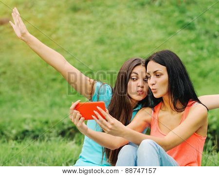 Two Women Friends Taking Pictures Of Themselves With Smart Phone On Picnic At The Park