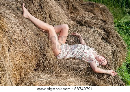 Young pretty woman relaxes on hay
