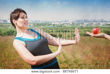 Beautiful Plus Size Woman In Sportswear Refusing Healthy Food