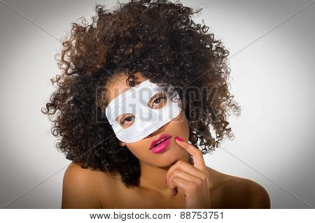 young woman with short curly dark hair wearing a mask