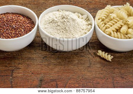 gluten free quinoa grain, flour and pasta - three small ceramic bowls against rustic wood with a copy space