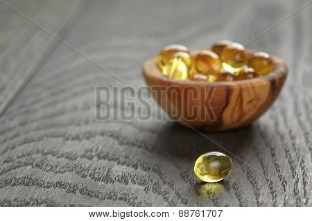 fish oil capsules in wood bowl on wooden table