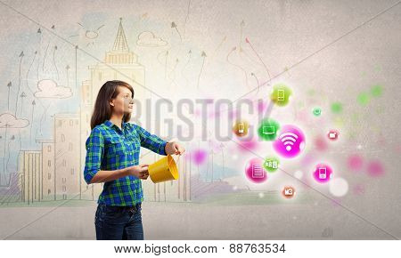 Young woman in casual holding yellow bucket with icons