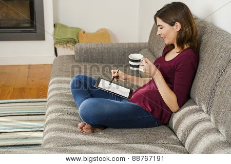 Beautiful woman at home in the sofa and working with a tablet