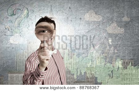 Funny image of young man looking in magnifying glass