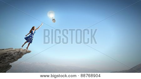 Happy young woman dreaming to fly in sky