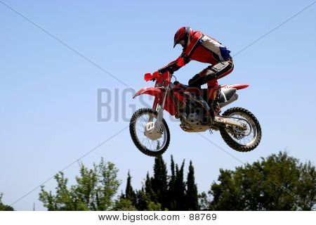 Orange And Red Moto X Or Moto Cross Bike Jumping Over Hump On Dirt Track.