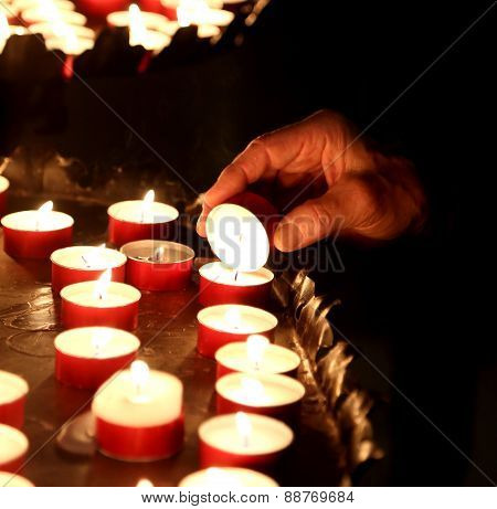 Hand Of An Elderly Woman Lights A Candle To Pray