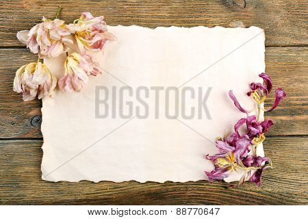 Dried flowers on sheet of paper on wooden table, top view