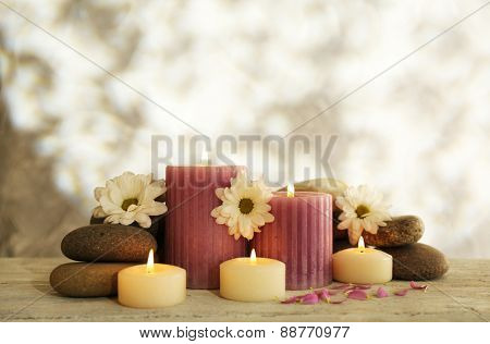 Still life with spa candles on light wallpaper background