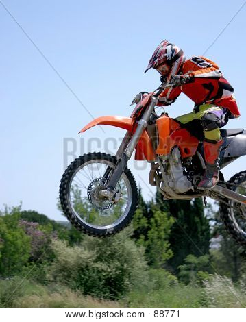 Red And Orange Moto-x Or Motor Cross Bike Giving Big Air On Dirt Track In The Sun