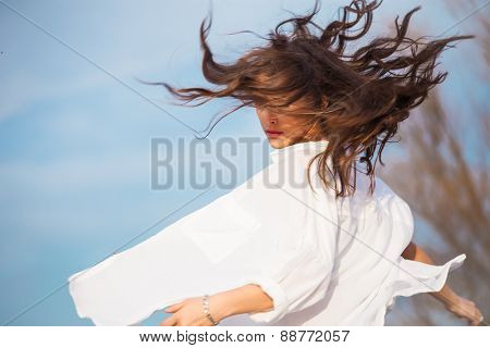young woman in white shirt with hair in motion, outdoor spring day, blue sky in background
