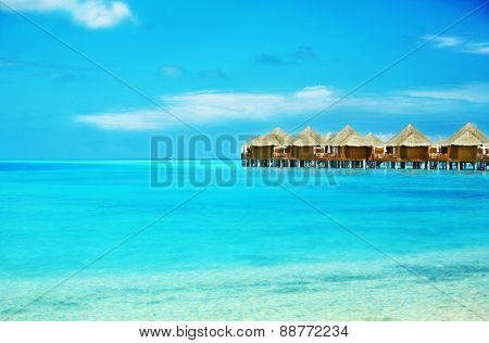 View of beautiful blue ocean water and bungalows in Baros Maldives