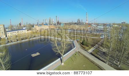 MOSCOW, RUSSIA - APRIL 11, 2014: Small park with pond near Oil Refinery of Gazpromneft company in sunny spring day, aerial view