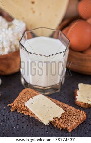 still life with dairy products as milk, cheese cottage cheese eggs and bread