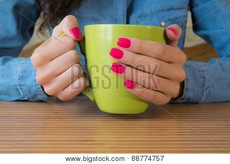 Hands Of A Young Girl With Red Nail Polish Holding A Large Green Cup