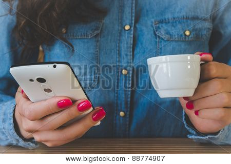 Girl In A Denim Shirt Drinking Coffee And Enjoys The Phone
