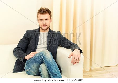 Handsome young man sitting relaxed on a sofa.