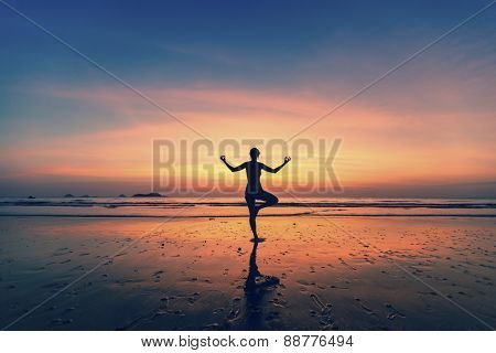 Yoga silhouette. Woman doing meditation near the ocean.