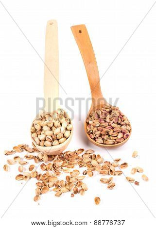 Two wooden spoons with pistachios