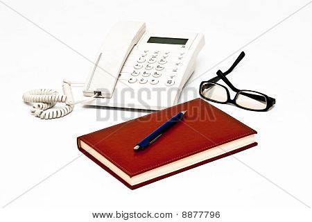 Telephone with glasses, pen and agenda isolated on white