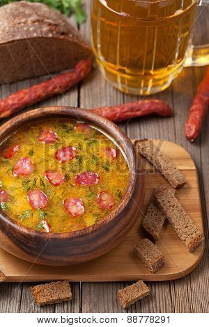 Traditional beer soup with sausage croutons and bread on vintage