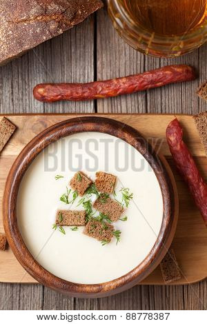 Traditional white beer cream soup with dill croutons and sausage