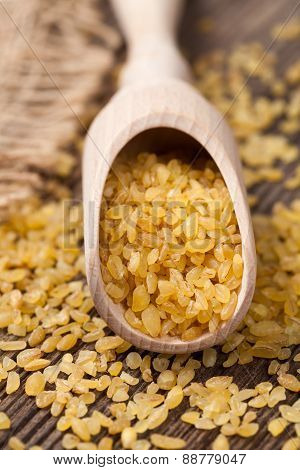 Natural super foods bulgur wheat grain in spoon close up