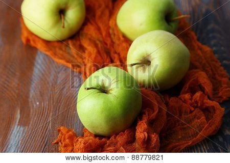 Green apples on wooden table on fabric, closeup