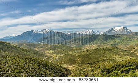 Snow Capped Mountains Of Corsica With Lush Green Valleys