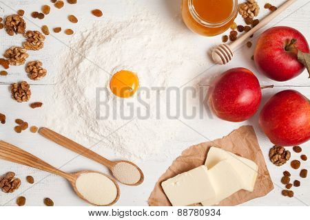 American apple pie preparation in rustic kitchen. Raw ingredients on white table