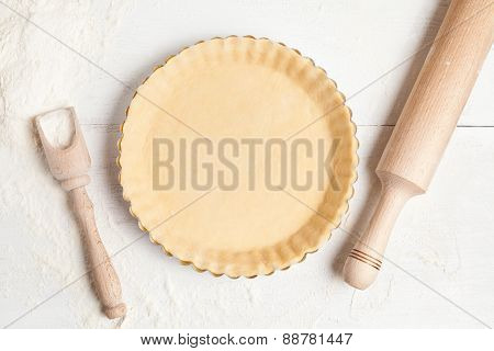Tart pie preparation, dough with yeast and rolling pin on white kitchen table