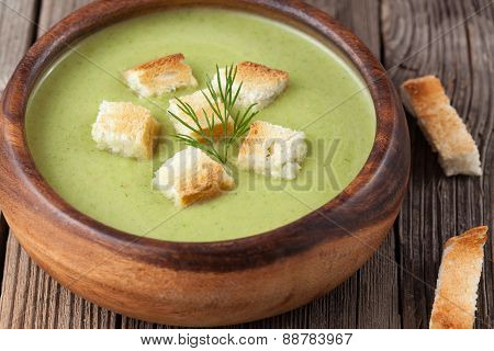 Healthy green cream broccoli soup with dried crusts in bowl