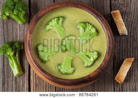 Delicacy cream of broccoli vegetarian soup in wooden bowl with croutons