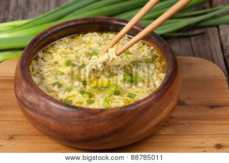 Traditional ethnic egg drop soup restaraunt recipe with food sticks holding pieces of eggs
