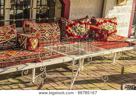 Eastern Divan with cushions and a glass table in a cafe