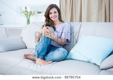 Happy brunette on couch smiling at camera at home in the living room