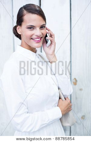 Pretty woman on the phone in front of wooden grey planks