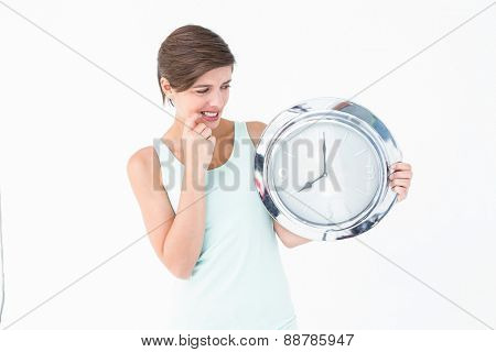 Stressed woman looking at clock on white background