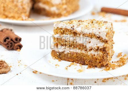 Piece of sliced gourmet carrot cake dessert with sweet cream and walnut