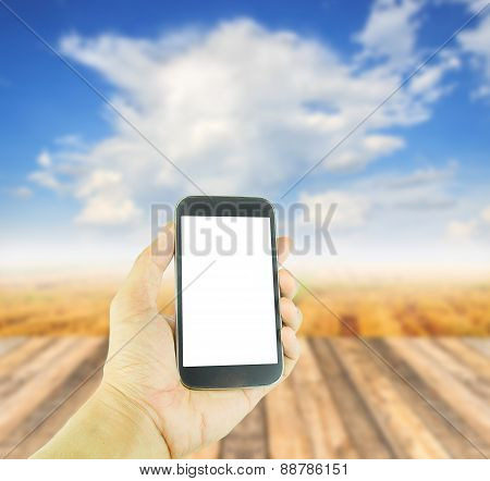 Hand Holding Smart Phone On Blurred Wooden Table Background