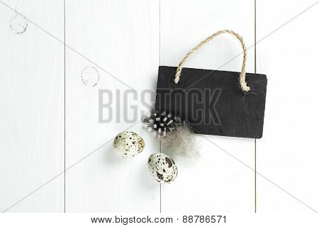 Quail Eggs And Feather With Vintage Blackboard On White Wooden Background