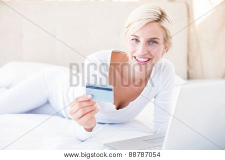 Smiling blonde woman doing online shopping in her bedroom