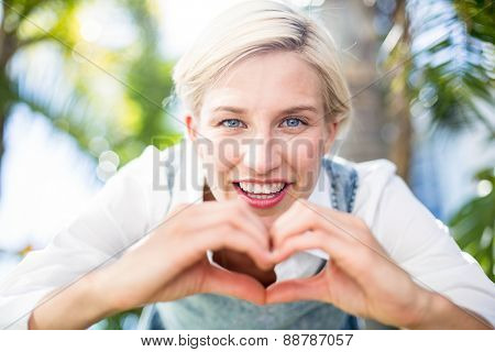 Pretty blonde woman smiling at the camera and doing heart shape with her hands in the park