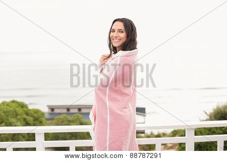 Beautiful woman wrapped in towel on the patio