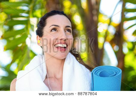 Fit beautiful brunette listening music and holding exercise mat on a sunny day