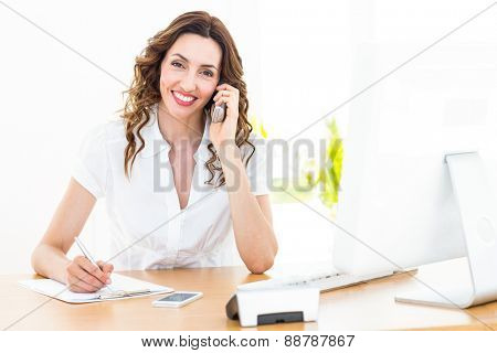 Smiling businesswoman having phone call on white background