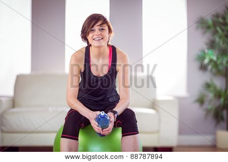 Fit woman with bottle on exercise ball at home in the living room