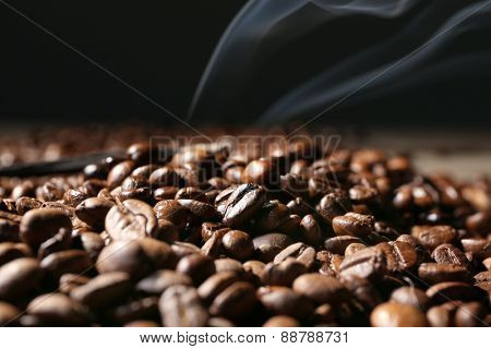 Pile of coffee beans on wooden table on dark background