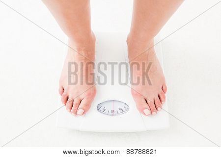 Womans feet on scales on white background